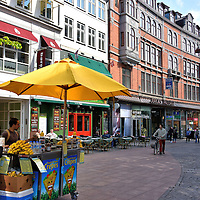 Strøget Shopping District in Copenhagen, Denmark <br /> Strøget is the main shopping district in central Copenhagen. The cobblestoned, pedestrian street stretches for 1.1 kilometers which make it one of the longest in Europe.  It is flanked by charming often historic buildings including one that dates back to 1616. Here you will find anything you need, from luxury retailers to street vendors for a quick bite to eat.