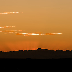 Sumbeams irradiate behind the mountains after sunset.
