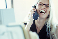 A young businesswoman laughing while talking on the telephone.
