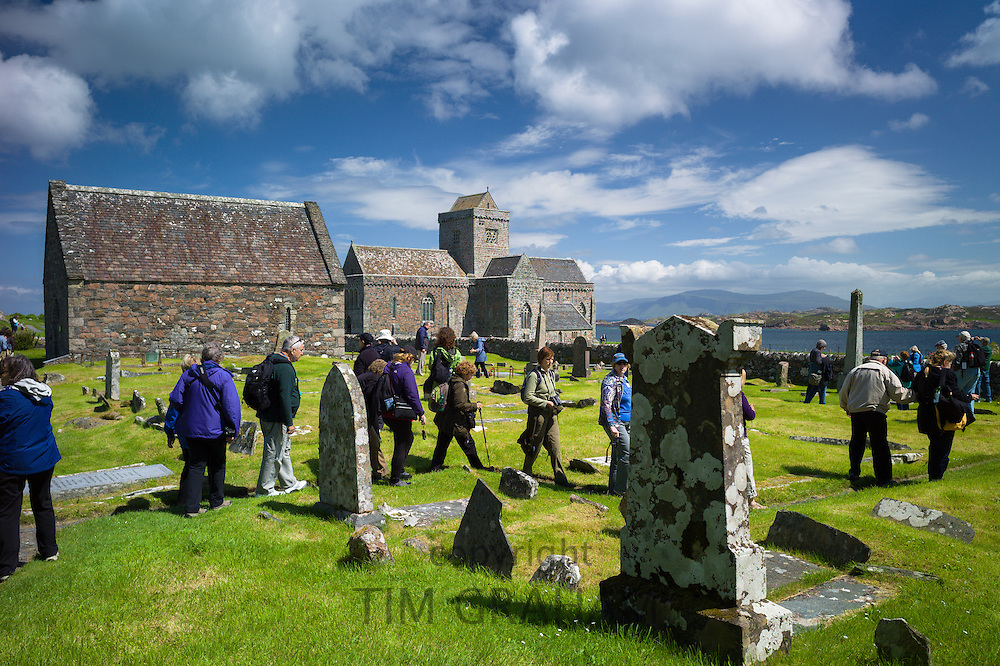 Tourists visiting the St Oran's Cemetery, Reilig Odhrain, where kings and clan chiefs are buried on Isle of Iona in Scotland