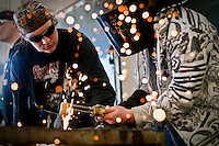 JEROME A. POLLOS/Press..Erik Satren, left, a North Idaho College student and volunteer for the Hard Hats, Hammers and Hot Dogs event, instructs Brian Johnson, 15, from Post Falls High School, how to use a cutting torch.