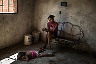 "OCUMARE DEL TUY, VENEZUELA - OCTOBER 11, 2017: Andreina del Valle Merchán, 25, watches over her malnourished 5-year-old daughter, who only weighs 11 pounds, at their family home in an abandoned government housing project. Six weeks after her 17-month-old nephew Kenyerber's death from severe malnutrition, Ms. Merchán's family is still struggling with hunger on a daily basis. They pass up to five days at a time without eating anything - only drinking water to ease their hunger pangs. ""This is a nightmare,"" she said, describing how the children start to vomit, sweat, and become sluggish after days of not eating. ""It is horrible,"" she said. Ms. Merchán and her family have made their home in an abandoned government housing project, with no running water nor indoor plumbing, and jury-rigged electricity - in order be able to spend all of their money only on food. The only food in the entire house this day was half a bag of salt, and one lime. PHOTO: Meridith Kohut for The New York Times"