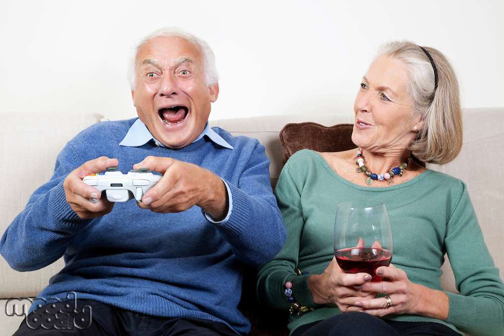 Happy senior woman with wine glass looking at excited spouse playing video game