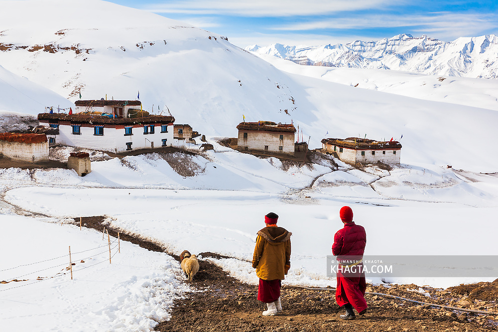 Lama Namo and Angchuk walking towards Komic village to perform a prayer in a house.