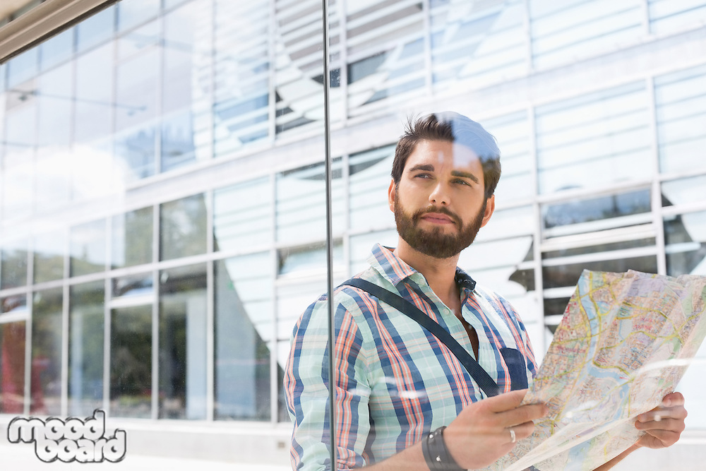 Thoughtful man looking away while holding road map against glass wall