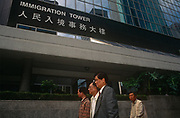 Hong Kong Chinese walk beneath the ImmigrationTower in Central, a year before the handover of sovereignty from Britain to China, on 29th March 1996, in Hong Kong, (then a British colony but latterly, China).