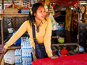 "14 FEBRUARY 2019 - SIHANOUKVILLE, CAMBODIA: A Cambodian woman who moved to Sihanoukville with her family in her snack stand on a construction site in Sihanoukville. She said they moved to Sihanoukville about a month ago hoping to find jobs in the Chinese financed boom in Sihanoukville. Her husband works as a construction laborer and she runs a small drink and snack stand. There are about 80 Chinese casinos and resort hotels open in Sihanoukville and dozens more under construction. The casinos are changing the city, once a sleepy port on Southeast Asia's ""backpacker trail"" into a booming city. The change is coming with a cost though. Many Cambodian residents of Sihanoukville  have lost their homes to make way for the casinos and the jobs are going to Chinese workers, brought in to build casinos and work in the casinos.      PHOTO BY JACK KURTZ"