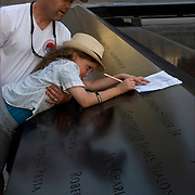 At sunset, father is holding and helping his daughter at the memorial to trace the name of a love one who lost their life on 9/11/01. <br />