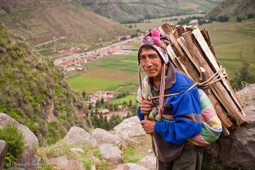 A wood seller with a view of the town of Pisac, Peru.