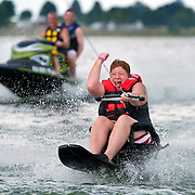 "Cara Combs pumped her fist after successfully water skiing over the pull boat's wake during the 18th annual ""Day at the Lake"" on Friday at Smithville Lake. Combs, an Army veteran who lost the use of her legs in 1993, water skied for the first time Friday at the event sponsored by the Rehabilitation Institute of Kansas City and Ameristar for those with spinal cord injuries, amputees or the blind. Activities included kayaking, hand cycling, jet skiing, water skiing and boat rides."