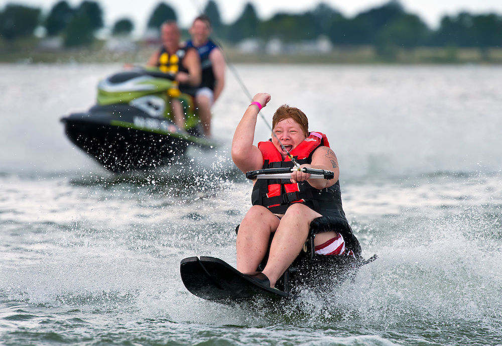 """Cara Combs pumped her fist after successfully water skiing over the pull boat's wake during the 18th annual """"Day at the Lake"""" on Friday at Smithville Lake. Combs, an Army veteran who lost the use of her legs in 1993, water skied for the first time Friday at the event sponsored by the Rehabilitation Institute of Kansas City and Ameristar for those with spinal cord injuries, amputees or the blind. Activities included kayaking, hand cycling, jet skiing, water skiing and boat rides."""