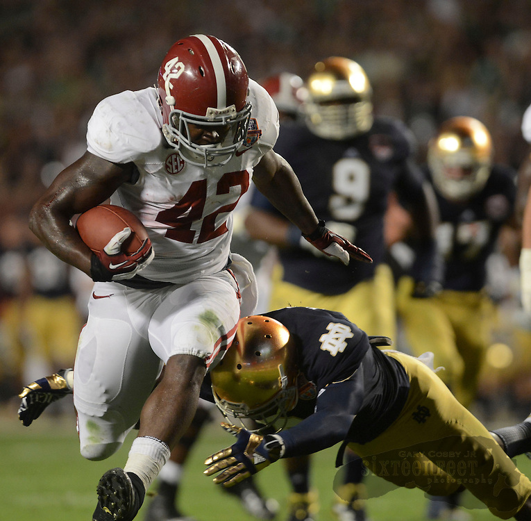 Daily Photo by Gary Cosby Jr.   Alabama running back Eddie Lacy (42) powers through the Notre Dame defensive for a large gain during the first half of the BCS National Championship Game in Sun Life Stadium Monday, January 7, 2013.