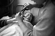 China's Aging Population 4 - A senile patient cries as her fingernails are cut by an attendant.