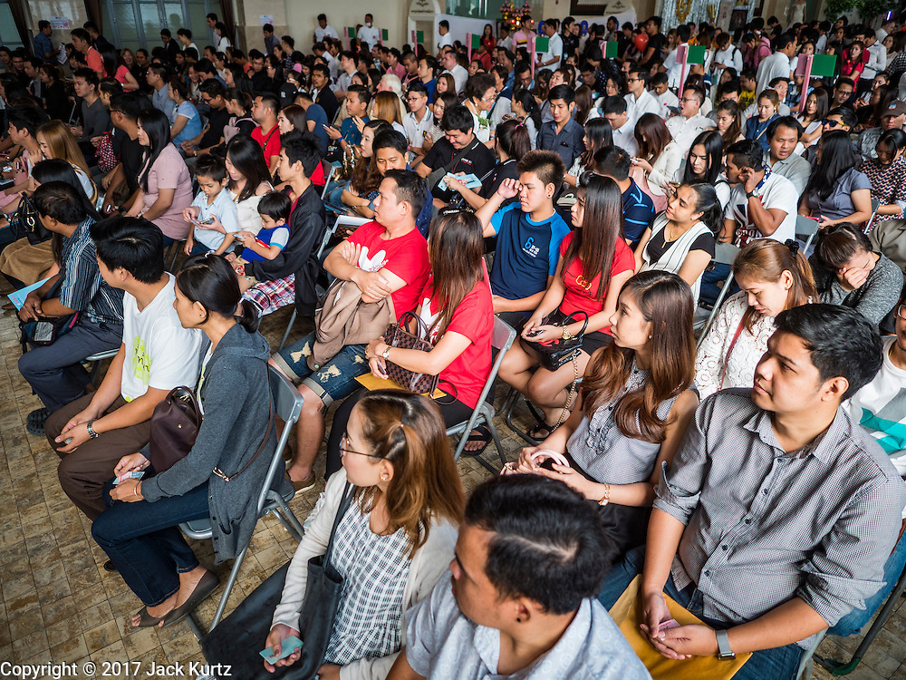 "14 FEBRUARY 2017 - BANGKOK, THAILAND: People wait to get register their marriages in the Bang Rak district in Bangkok. Bang Rak is a popular neighborhood for weddings in Bangkok because it translates as ""Village of Love."" (Bang translates as village, Rak translates as love.) Hundreds of couples get married in the district on Valentine's Day, which, despite its Catholic origins, is widely celebrated in Thailand.      PHOTO BY JACK KURTZ"