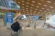 Nederland, the Netherlands, Arnhem, 1-9-2015Het nieuwe station van de gelderse hoofdstad wordt binnenkort officieel geopend. De ov terminal met parkeergarage en fietsenstalling is klaar. Een man in een rolstoel bekijkt het gebouw. De ingewikkelde architectuur heeft het bouwproject veel problemen en vertraging opgeleverd. Het is dan ook een architectonisch en bouwkundig hoogstandje. Het ontwerp voor het station is gedaan door architectenbureau UNStudio, Ben van Berkel.  Uiteindelijk heeft de bouw 18 jaar en 90 miljoen euro, veel meer als aanvankelijk begroot, gekost. Meteen deden zich al enkele valpartijen voor op een van de onregelmatige trappen, zodat een opgang tijdelijk afgesloten werd totdat er duidelijke trapmarkering is aangebracht...FOTO: FLIP FRANSSEN/ HH