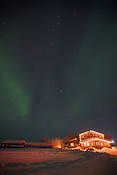 The northern lights glow over Bettles Lodge at the Arctic Circle in Alaska.