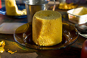 A savory cornmeal cake steamed in a tin-can contraption invented by Francisco Da Silva Correia, a rancher who lives with his wife, Solange,  and family in a riverside home near the town of Caviana in Amazonas, Brazil.  (Solange Da Silva Correira is featured in the book What I Eat: Around the World in 80 Diets.)