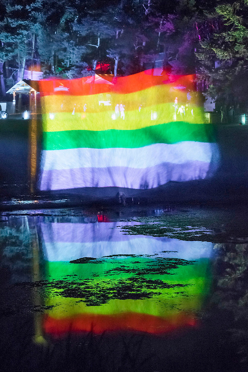 A light show projected on a wall of spray celebrates the festivals 11th year and theme of Love thy Neighbour (aimed at refugees, minorities and the recent Brexit) - The 2016 Latitude Festival, Henham Park, Suffolk.