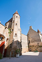 Towers and turrets of the inner courtyard of Chateauneuf-en-Auxois against a lovely blue sky.