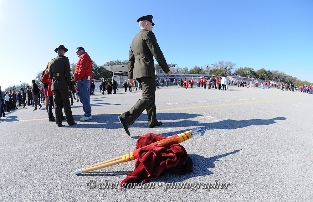 A new Marine Corps private walks past a disassembled platoon guidon after a graduation ceremony on the parade deck at the Marine Corps Recruit Depot (MCRD) in Parris Island, SC on Friday, March 15, 2013.