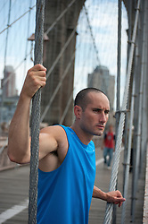 athletic man stopping to take a break on The Brooklyn Bridge in New York City
