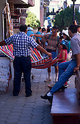 Tourists shopping for a Mexican blanket, vendor displaying one for them, Nogales, Sonora, Mexico..©1990 Edward McCain. All rights reserved. McCain Photography, McCain Creative, Inc.