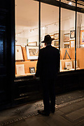 A man wearing a hat stands looking at paintings in the window of an art gallery, on 15th January 2018, London, England.