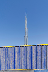 Burj khalifa tower behind barrier at construction site in Dubai United Arab Emirates