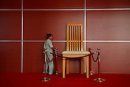 A worker polishes the security cordon surrounding a very large chair set as decoration at the entrance to the plenary session room for the World Economic Foum in Dalian, China, Wednesday, Sept. 9, 2009.