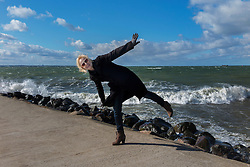 Woman standing on Merivälja pier in Tallinn. Windy weather.