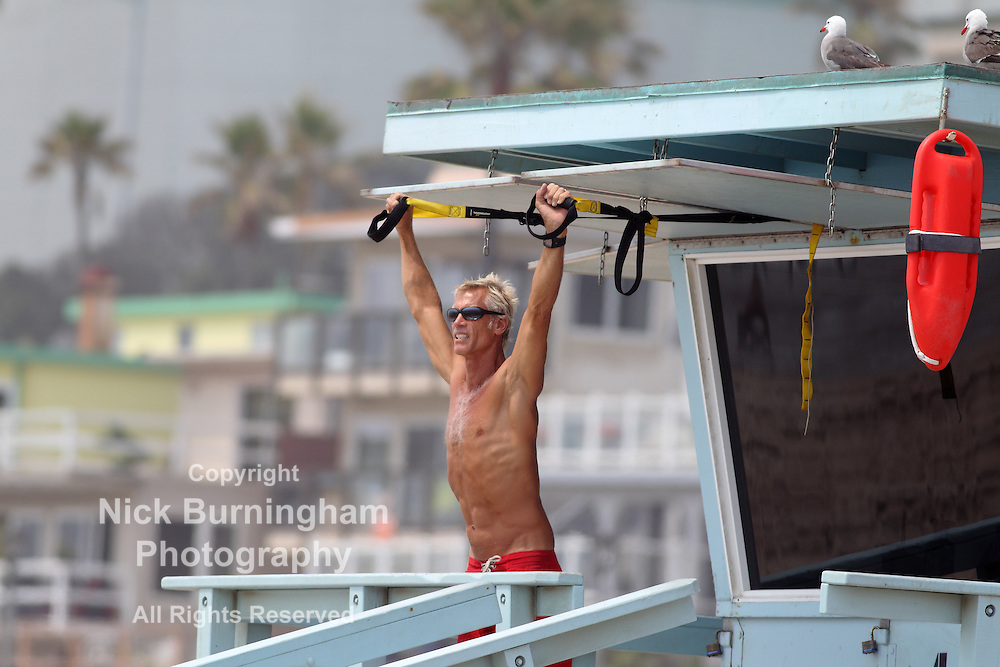 MANHATTAN BEACH, CALIFORNIA, USA - JULY 1, 2013. A lifeguard stretches as he watches the surfers on July 1, 2013. People flocked to the ocean to escape the heatwave inland.