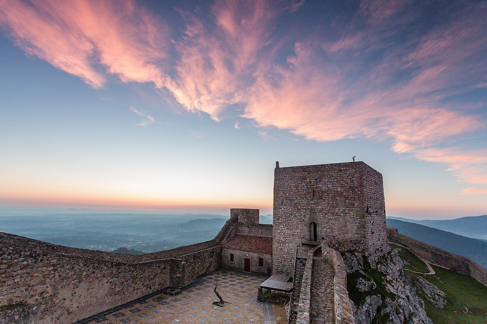 Cirrus clouds turned pink by the sunrise light float over the Castle at Marvão.