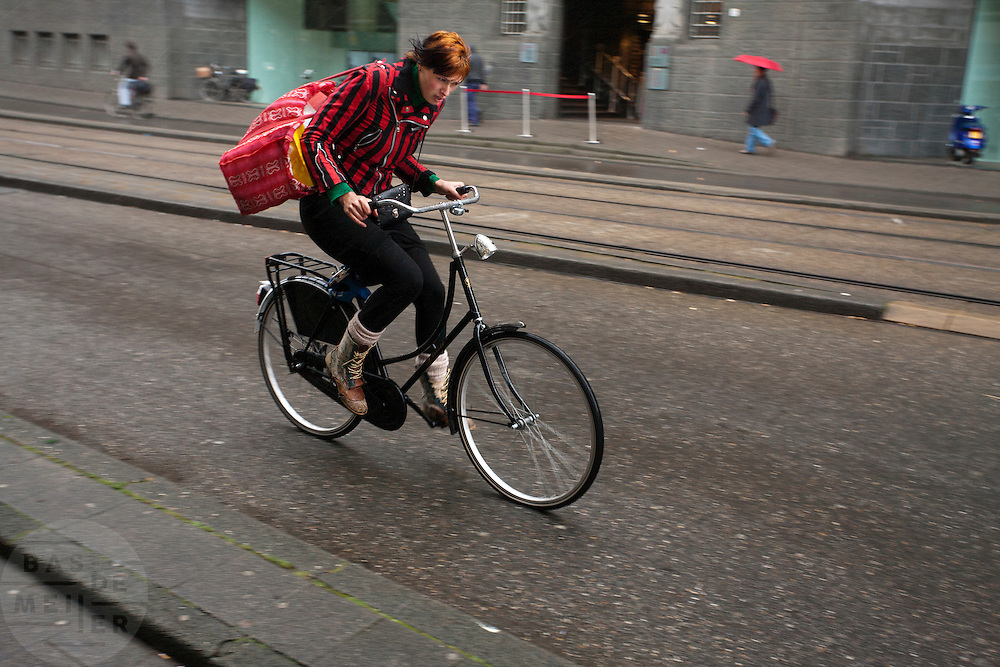 Een meisje fietst in de regen door de Vijzelstraat in Amsterdam.<br /> <br /> A girl is cycling in the rain at the Vijzelstraat in Amsterdam