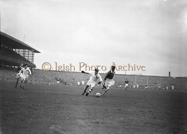 Galway and Cork players both attempt to kick the ball during the All Ireland Senior Gaelic Football Championship Final, Cork v Galway in Croke Park on the 7th October 1956. Galway 2-13 Cork 3-7.