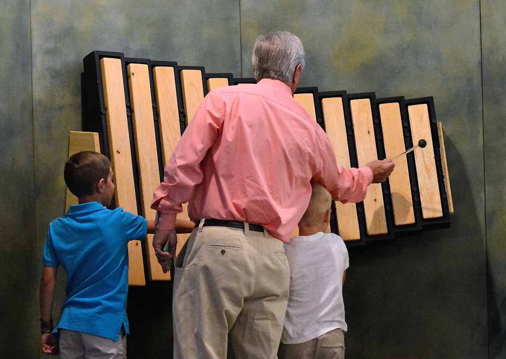 jt062717f/arts/jim thompson/ Perry Williams with his grandkids (left to right) Stone and Benjamin Williams as they  play with the wooden xylophone that is one of the  exhibits of the Wild Music: Sounds and Songs of Life Exhibit at the New Mexico Museum of Natural History and Science.Tuesday June. 27, 2017. (Jim Thompson/Albuquerque Journal)