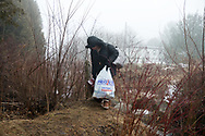 February 25, 2017 - Hemmingford, Quebec : A woman from Sudan carries her belongings across the Canadian border on Roxham Road in southern Quebec.
