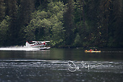 A seaplane takes off past a couple kayaking in Misty Fiords National Monument, Alaska.