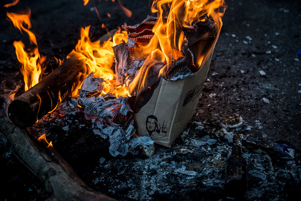 "CARACAS, VENEZUELA - MAY 8, 2017:  Members of ""The Resistance"" burn a box used for rationed food distributed by the Socialist government, with a drawing of late President Hugo Chávez, to use as a roadblock during clashes with state security forces.  The streets of Caracas and other cities across Venezuela have been filled with tens of thousands of demonstrators for nearly 100 days of massive protests, held since April 1st. Protesters are enraged at the government for becoming an increasingly repressive, authoritarian regime that has delayed elections, used armed government loyalist to threaten dissidents, called for the Constitution to be re-written to favor them, jailed and tortured protesters and members of the political opposition, and whose corruption and failed economic policy has caused the current economic crisis that has led to widespread food and medicine shortages across the country.  Independent local media report nearly 100 people have been killed during protests and protest-related riots and looting.  The government currently only officially reports 75 deaths.  Over 2,000 people have been injured, and over 3,000 protesters have been detained by authorities.  PHOTO: Meridith Kohut"