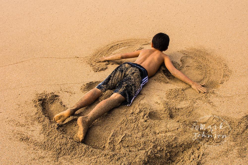 """Boy making a """"sand angel"""" on Kalalau Beach, Na Pali Coast, Kauai, Hawaii"""