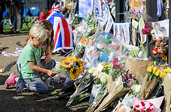 © Licensed to London News Pictures. 31/08/2017. London, UK. Noah and Matilda place flowers at the gates to Kensington Palace in London on the 20th anniversary of the death of Diana, Princess of Wales. Princess Diana was fatally injured in a car crash along with her companion Dodi Fayed, while the couple were being driven through the Pont de l'Alma tunnel in Paris on 31 August 1997. Photo credit: Ben Cawthra/LNP