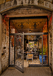 About the Subject: A passageway, originally built to give access for horse-drawn carriages, now a caf&eacute; with an elaborate entrance gate.<br /> <br /> About the Capture: Taken in the morning, in early Spring, this semi-alfresco caf&eacute; reaches through the passageway, lined with exposed brick and stone, to an inner courtyard. The gate is welcomingly ajar. The rich textures and earthy colours give a sense of warmth despite being in the open air while the heavy stone construction and wrought iron gates impart a feeling of strength and substance. The presentation in this capture accentuates the colours, contrasts, strength and inviting warmth of the scene.