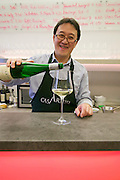 Vienna, Austria. Kiang Winebar.<br /> Joseph Kiang pouring a glass of wine..