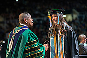 President McDavis congratulates Maria Gaston during fall commencement. Photo by Ben Siegel