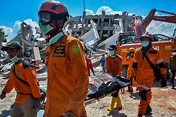 Oct. 1, 2018 - Palu, Indonesia - Rescue members transfer a body at a collapsed hotel in Palu. Over 1,203 people were killed in Palu, Donggala district, Parigi Mountong district and North Mamuju district, according to officials. Over 1,203 people were killed in Palu, Donggala district, Parigi Mountong district and North Mamuju district, after the 7.7 magnitude earthquake and the following tsunami. (Credit Image: © Iqbal Lubis/Xinhua via ZUMA Wire)