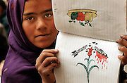 A young Afghan girl shows a drawing depicting war in Kabul, Afghanistan. 2002