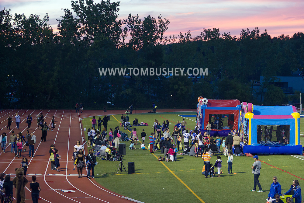 """Middletown, New York - Children play games with Middletown High School athletes at Faller Field during Family Fun Night on May 17, 2013. After dark """"The Lorax"""" was shown on the stadium screen. ©Tom Bushey / The Image Works"""
