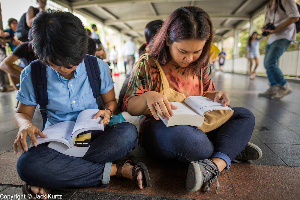 "31 MAY 2014 - BANGKOK, THAILAND: Women sit in the Skywalk between the BTS Skytrain Siam and Chit Lom stations to silently read George Orwell's ""1984"" and other books about civil disobedience and nonviolent protest. The protests are based on the ""Standing Man"" protests that started in Turkey last summer. Authorities made no effort to stop the protest or interfere with the people who were reading. Bangkok was mostly quiet Saturday. There were only a few isolated protests against the coup and military government.    PHOTO BY JACK KURTZ"