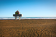 lifeguard tower standing strong in the sand against the blue sky background and surf at bethells, west auckland, new zealand
