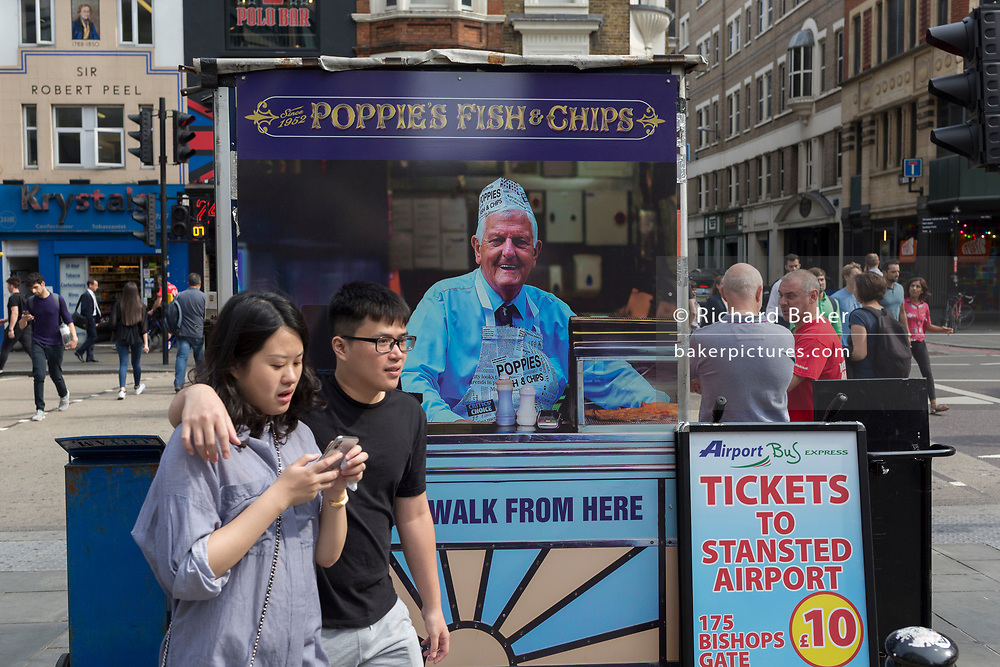 An Asian couple walk past the rear of a newspaper vendor's kiosk outside Liverpool Street mainline station in the City of London - the capital's financial district, on 3rd September 2018, in London England.
