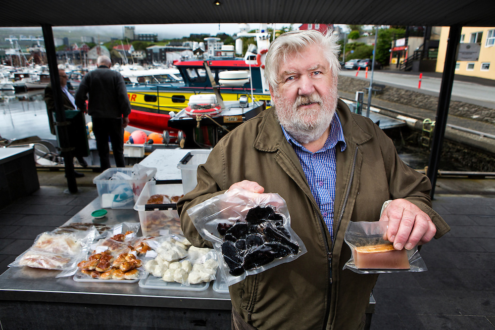 M&aring;rten Johannesen, a 71 year old retired boat captain supplements his finances by selling fish and pilot whale meat in Torshavn harbor on the island of Streymoy.  Marten says half his customers are tourists-curious to try the dried whale meat.  Johannesen himself eats the whale meat once a week.  He believes that the islanders will continue hunting-a process that is now &quot;fully controlled, and compassionate towards the animals.&quot;<br /> <br /> Johannessen holds up samples of dried pilot whale meat (left) and pilot whale blubber (right).<br /> <br /> Torshavn Harbor, Streymoy Island, Faroe Islands.